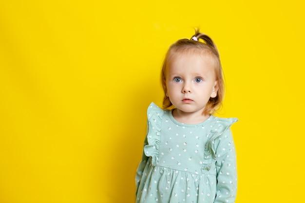Retrato de uma menina de bebê fofo com olhos azuis em um fundo amarelo. um lugar para texto. foto de alta qualidade