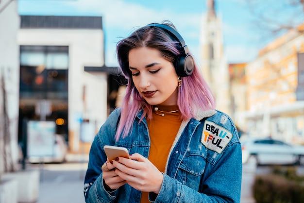 Retrato de uma menina de cabelo roxa que usa o telefone e a música de escuta em fones de ouvido.