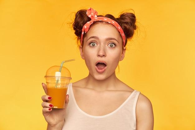 Retrato de uma menina de cabelo vermelho atraente com uma faixa vermelha pontilhada. vestindo camisa branca e segurando seu smoothie, expressando choque. assistindo isolado sobre a parede amarela