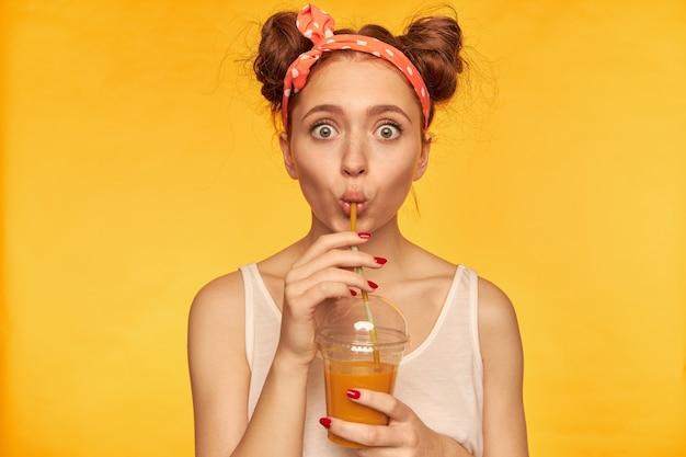 Retrato de uma menina de cabelo vermelho surpreso com uma faixa vermelha pontilhada. chocado com o gosto, tome um gole. vestindo camisa branca e segurando seu smoothie. assistindo isolado sobre a parede amarela