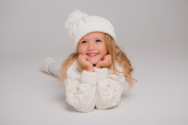 Retrato de uma menina de cabelos cacheados em um chapéu branco de malha de inverno