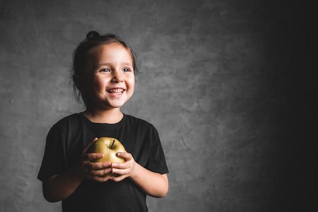 Retrato de uma menina de felicidade comendo uma maçã verde em fundo cinza.