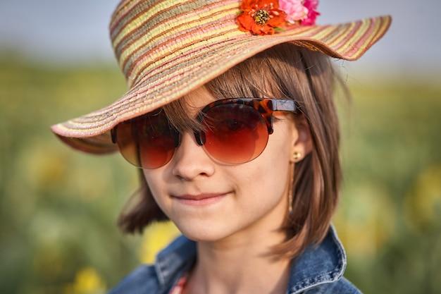 Retrato de uma menina de óculos de sol e chapéu