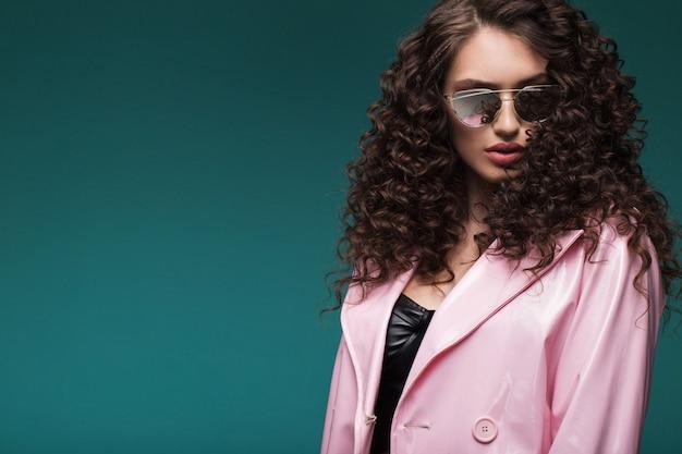Retrato de uma menina de óculos escuros e um casaco de laca rosa