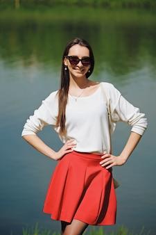 Retrato de uma menina de saia vermelha e blusa branca em pé na margem do rio