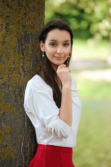 Retrato de uma menina de saia vermelha e blusa branca, encostado a uma árvore na margem do rio