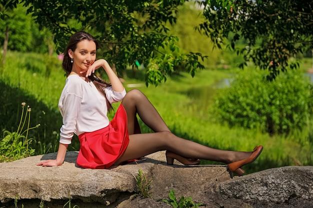 Retrato de uma menina de saia vermelha e blusa branca, sentado na pedra na margem do rio
