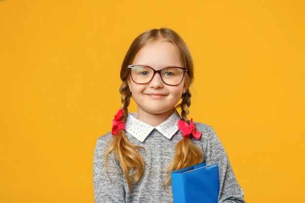 Retrato de uma menina de sorriso nos vidros com um livro.
