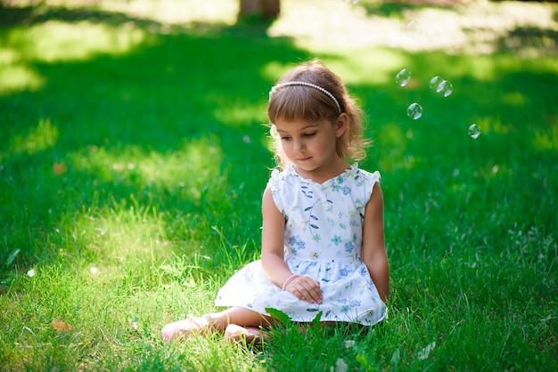 Retrato de uma menina de sorriso que senta-se na grama verde.