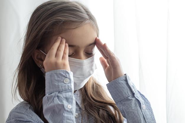 Retrato de uma menina do ensino fundamental com uma máscara protetora descartável