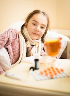 Retrato de uma menina doente deitada na cama tomando uma xícara de chá com limão