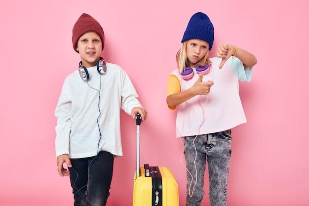 Retrato de uma menina e um menino com uma mala amarela nas mãos de fundo cor-de-rosa
