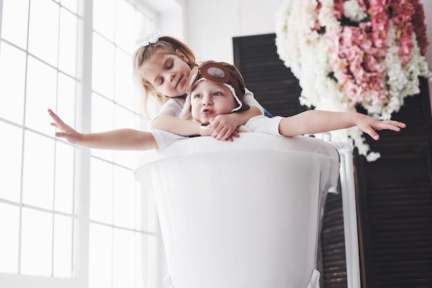 Retrato de uma menina e um menino de chapéu piloto jogando no banheiro em pilotos ou marinheiros. o conceito de viagem, infância e realização de sonhos