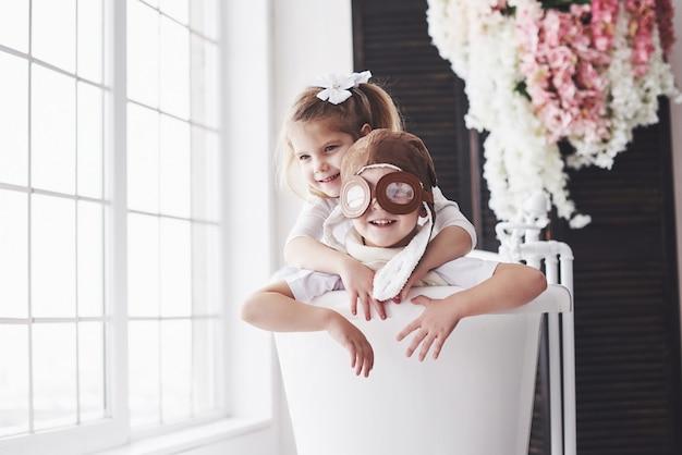 Retrato de uma menina e um menino de chapéu piloto jogando no banheiro em pilotos ou marinheiros. viagens, infância e realização de sonhos