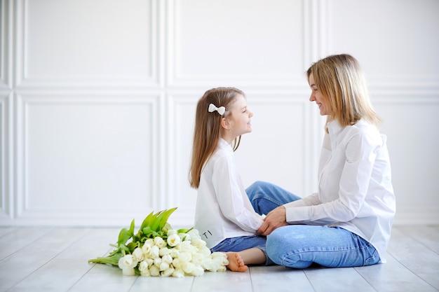 Retrato de uma menina e uma mãe amorosa com tulipas