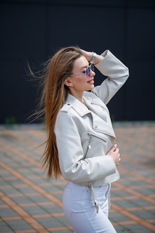 Retrato de uma menina elegante de cabelos compridos em uma blusa branca e jeans claro fica com um sorriso no contexto de uma parede cinza de um edifício em um dia ensolarado de primavera.