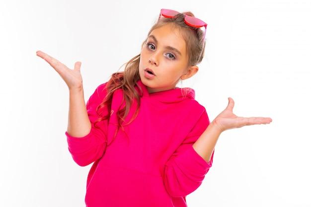 Retrato de uma menina elegante em moletom rosa, óculos de sol rosa não sabe o que fazer, isolado no fundo branco