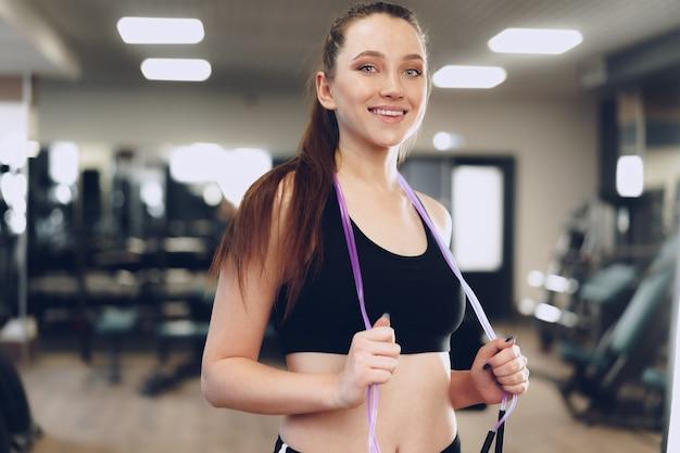 Retrato de uma menina em forma com pular corda em pé em uma academia