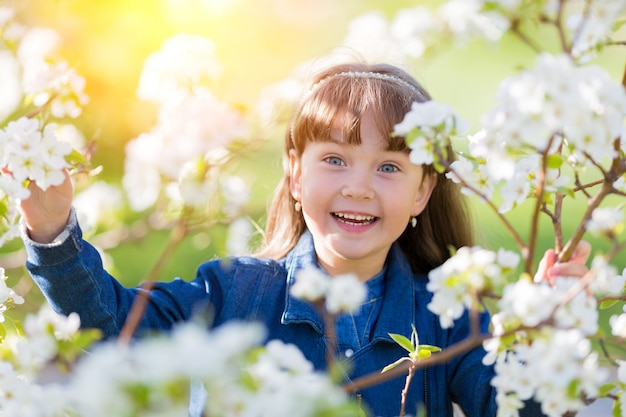Retrato de uma menina em macieira florescendo.