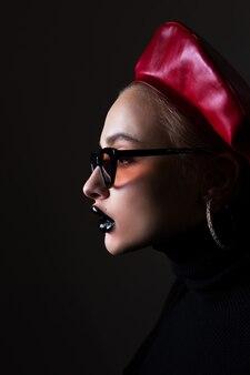 Retrato de uma menina em óculos de sol com batom preto nos lábios