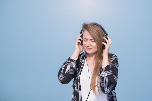 Retrato de uma menina em roupas casuais que fica feliz em ouvir música em fones de ouvido em um fundo azul