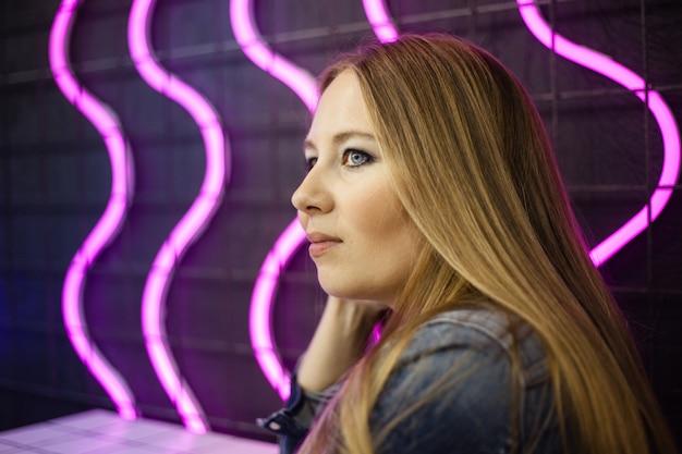 Retrato de uma menina em um café da cidade, iluminação neon e estilo da juventude