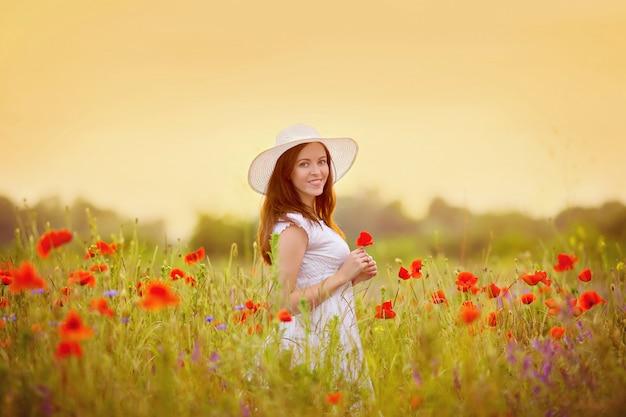 Retrato de uma menina em um campo de papoulas ao pôr do sol em um vestido branco e chapéu