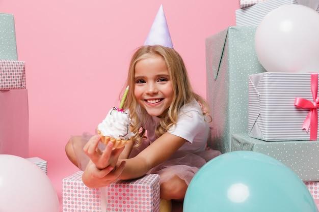Retrato de uma menina em um chapéu de aniversário comemorando