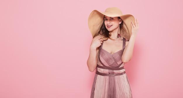 Retrato de uma menina em um chapéu de verão e vestido em uma parede rosa