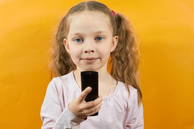 Retrato de uma menina em um fundo amarelo, segurando um controle remoto da tv.
