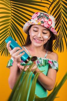 Retrato de uma menina em um maiô e chapéu, colocando protetor solar.