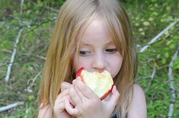 Retrato de uma menina em um prado de verão com decorações de flores do campo, comendo uma maçã