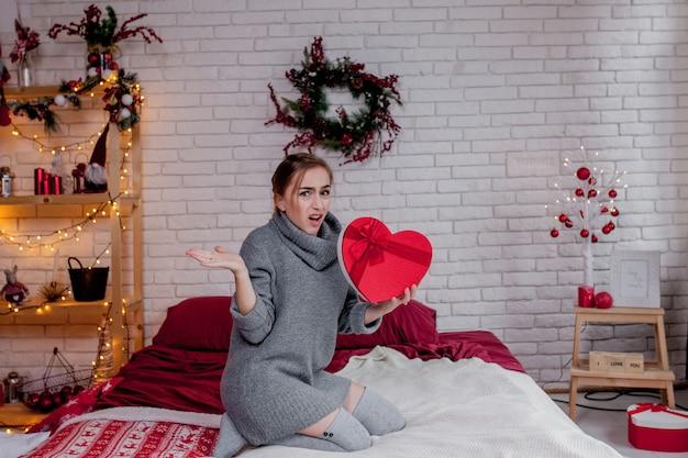 Retrato de uma menina em um suéter cinza com uma caixa de presente vermelha em forma de coração, sentado no apartamento, conceito de dia dos namorados, cópia espaço