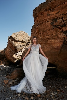 Retrato de uma menina em um vestido de noiva lindo posando um fotógrafo na praia. a noiva está nas pedras