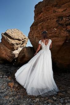 Retrato de uma menina em um vestido de noiva lindo posando um fotógrafo na praia.