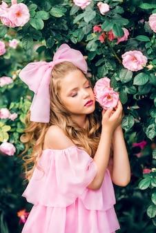 Retrato de uma menina em um vestido rosa com um grande laço entre flores. boneca menina em rosas