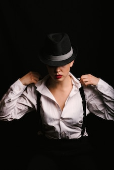 Retrato de uma menina em uma camisa branca com suspensórios e batom vermelho em um chapéu. foto com o grão jogado
