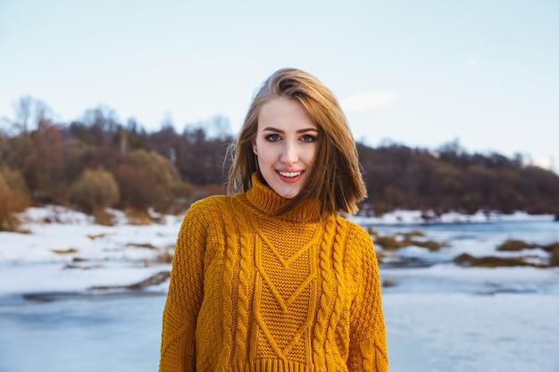 Retrato de uma menina em uma camiseta amarela e cabelo curto contra um céu azul e floresta do inverno.