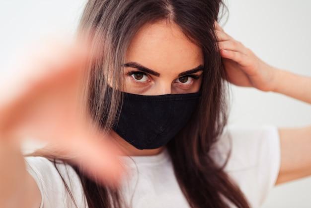 Retrato de uma menina em uma máscara médica preta e camiseta branca sobre um fundo branco, com a mão em primeiro plano. a quarentena da epidemia de coronavírus acaba de terminar