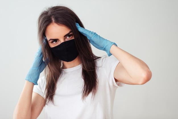 Retrato de uma menina em uma máscara médica preta e uma camiseta branca sobre um fundo branco, as mãos nas luvas perto da cabeça. sintomas de uma doença de coronovírus. ficar em casa conceito