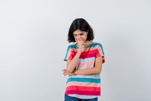Retrato de uma menina em uma pose de pensamento em uma camiseta e olhando deprimida.