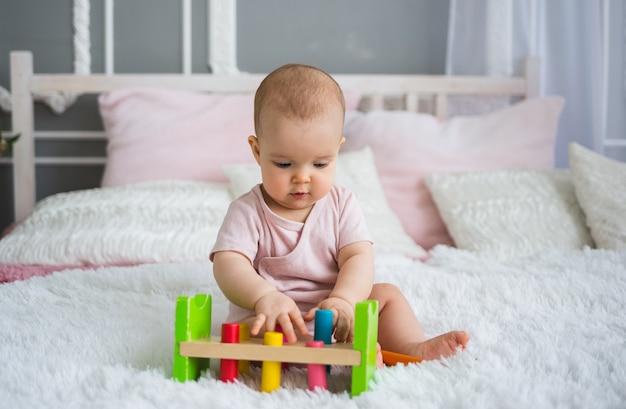 Retrato de uma menina em uma roupa rosa, sentada na cama e brincando com um brinquedo colorido de lógica. desenvolvimento na primeira infância