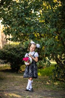 Retrato de uma menina em uniforme escolar, segurando um buquê de flores cor de rosa