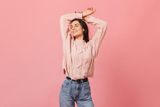 Retrato de uma menina encantadora com prazer posando com os braços levantados. mulher de blusa de malha e calça jeans mãe sorrindo com os olhos fechados.