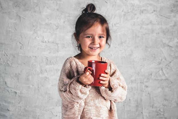 Retrato de uma menina encantadora com um suéter bege em fundo cinza