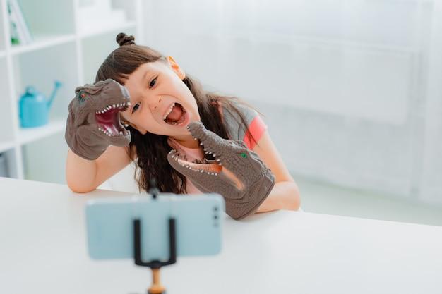Retrato de uma menina encantadora e alegre gesticulando um sinal de ok com o polegar e mostrando o brinquedo de dinossauro no smartphone