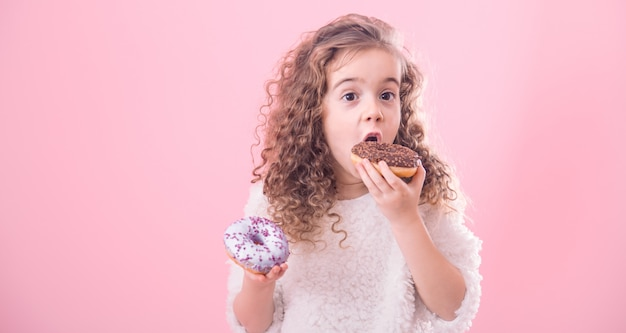 Retrato de uma menina encaracolada comendo rosquinhas