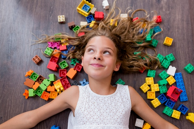 Retrato de uma menina engraçada bonito do pré-adolescente que joga com blocos do brinquedo da construção. deitado no chão de madeira, cercado de blocos coloridos crianças brincando.