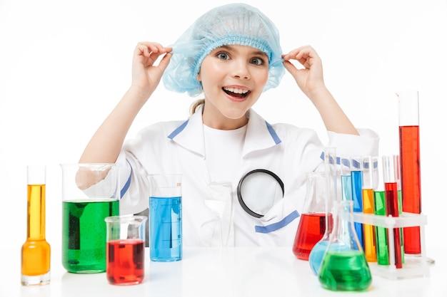 Retrato de uma menina engraçada com jaleco branco fazendo experimentos químicos com líquido multicolorido em tubos de ensaio isolados sobre uma parede branca