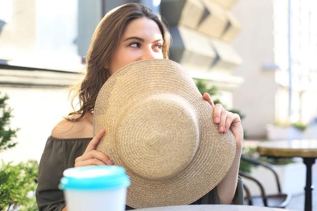 Retrato de uma menina escondendo o rosto atrás de um chapéu de palha enquanto está sentado no café de rua de verão.